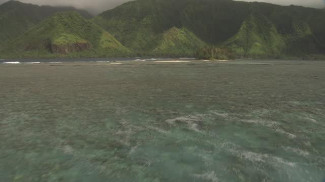 waves break onto coral reef at edge of tropical lagoon, tahiti, french polynesia - tahiti stock videos & royalty-free footage