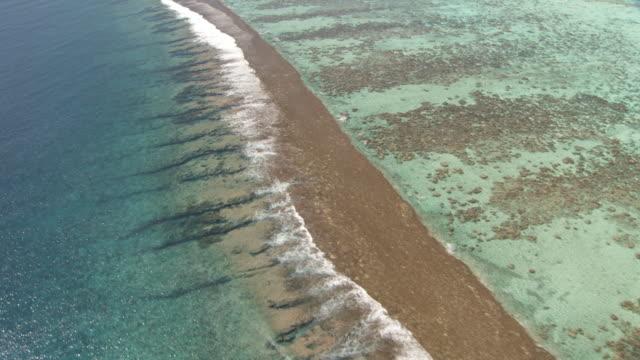 Waves break onto reef at edge of tropical lagoon, Maupiti, French Polynesia