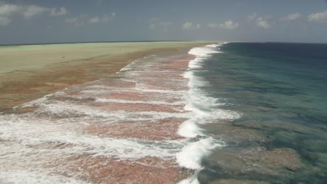 vidéos et rushes de waves break onto reef at edge of tropical lagoon, rangiroa, french polynesia - south pacific ocean