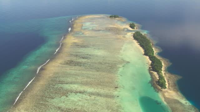 Waves break onto reef at edge of tropical lagoon, Solomon Islands