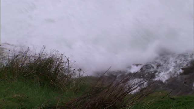 waves break over boulders along the irish coast. - boulder stock videos & royalty-free footage
