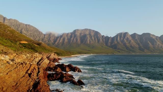 waves bricht gegen eine felsige küste - republik südafrika stock-videos und b-roll-filmmaterial