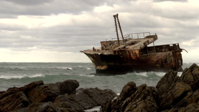 ms waves breaking against rocks with meisho maru 38/  trawler shipwrecked in 1982 in background / cape agulhas/ western cape/ south africa - imperfection stock videos & royalty-free footage