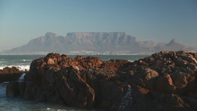 waves breaking against rocks with table mountain in the background - ライオンズヘッド点の映像素材/bロール