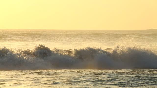 Waves breaking ashore at dusk