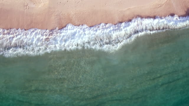aerial: waves breaking on a beach - riva dell'acqua video stock e b–roll
