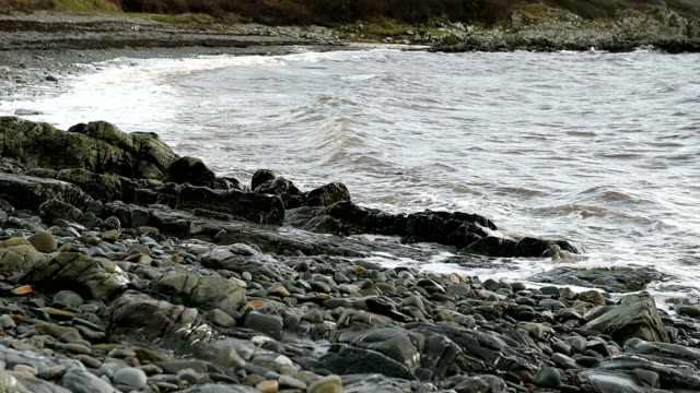 waves breaking on a rocky scottish shoreline - johnfscott stock videos & royalty-free footage