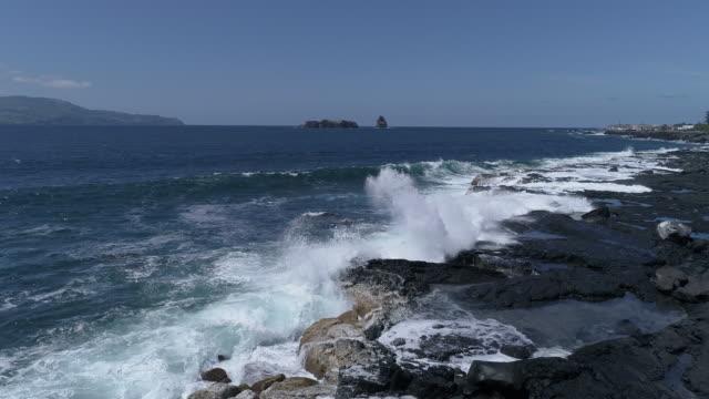 Waves breaking on black lava coast, slow motion aerial