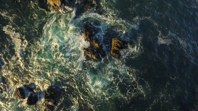 waves breaking on rocks Bird's eye view zoom out rotate