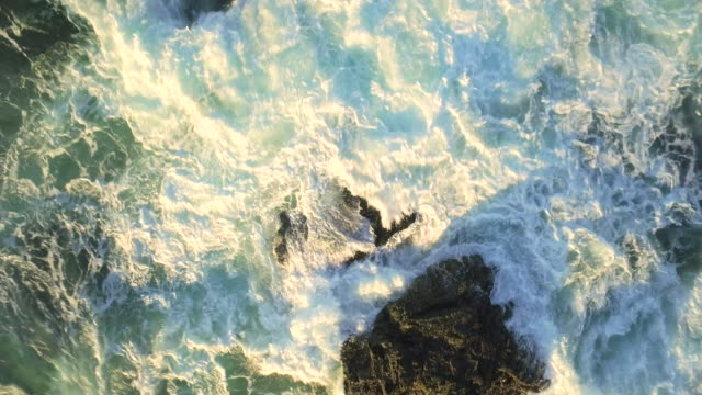 waves breaking on rocks Bird's eye view zoom rotate