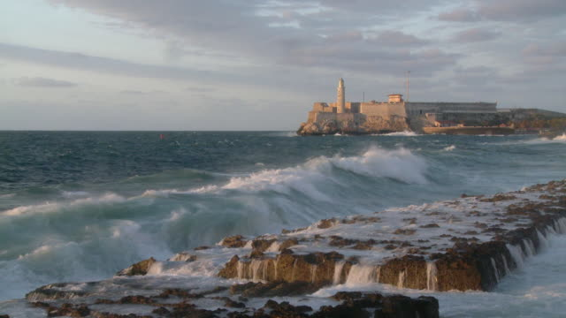 ws waves breaking on shore with el morro castle in distance / havana, cuba - fortress stock videos & royalty-free footage
