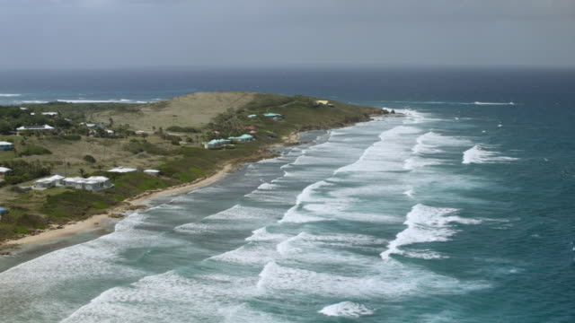 WS AERIAL POV Waves breaking over rocky cliffs to reveal Cabo de las Flechas / Sion Farm, St Croix, US Virgin Islands, United States