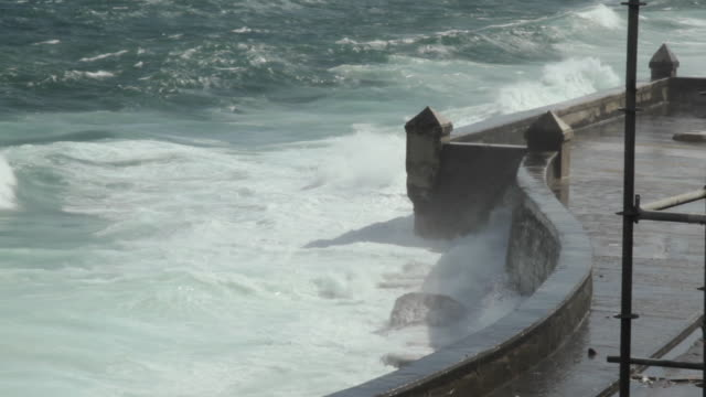 Waves crash against a sea wall in Havana.