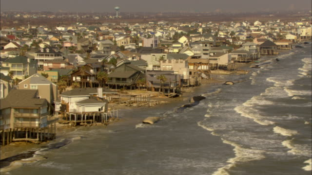 waves crash against hurricane damaged houses on a shoreline. - stilts stock videos and b-roll footage