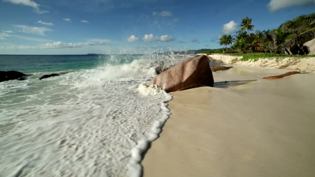 Waves crash against large boulders on a beach on Cousine Island.