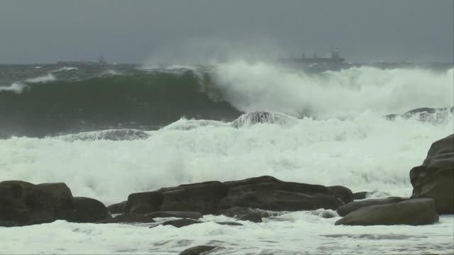 Waves crash against rocks on a beach while a ship sails past. Available in HD.