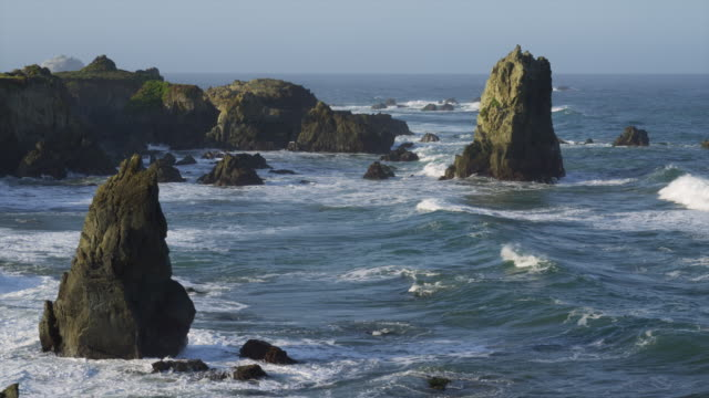 Waves crash against several rock formations in the Pacific Ocean.
