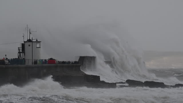 vídeos de stock e filmes b-roll de waves crash against the harbour wall during storm freya on march 3 at porthcawl wales the met office have issued a yellow weather warning for wind... - divisa