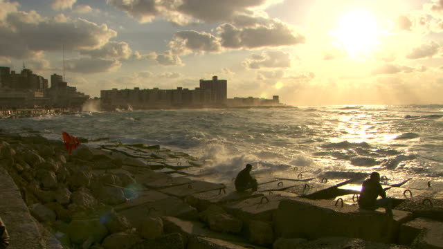 Waves crash against the rocks at Alexandria's harbour.