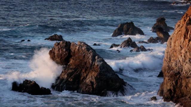 Waves crash along rugged Big Sur coast line California sunset