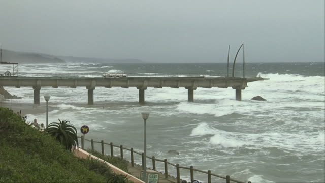Waves crash around the pier of Umhlanga Rocks. Available in HD.