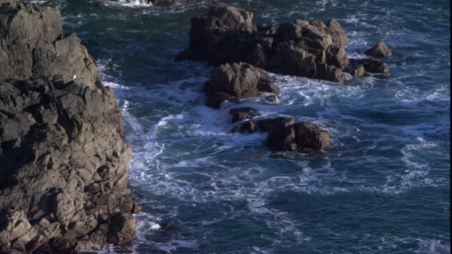 waves crash into a rocky english coastline. - channel islands england stock videos & royalty-free footage