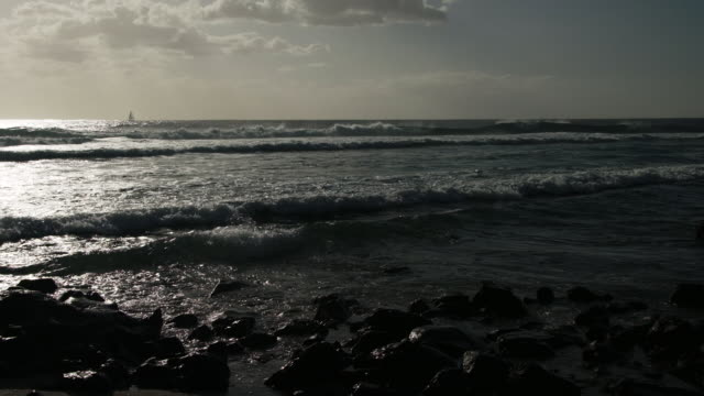 vidéos et rushes de waves crash into shoreline during sunset in slow motion - dom tom