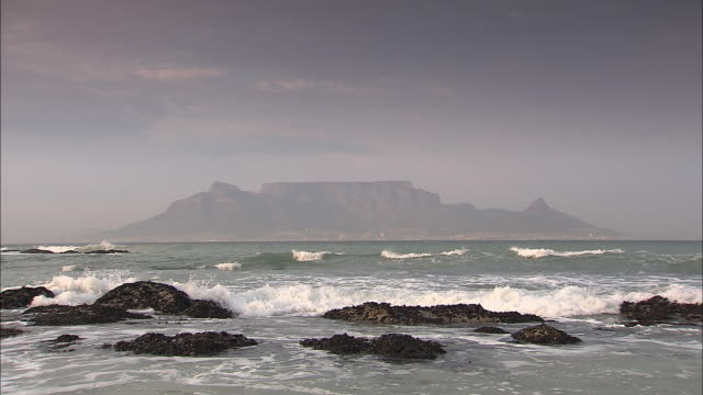 Waves crash into the rocks near the shore of the Cape Peninsula.