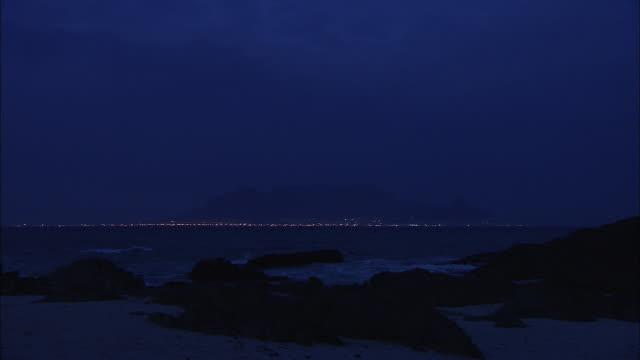 vídeos y material grabado en eventos de stock de waves crash on a rocky shore at night. - península