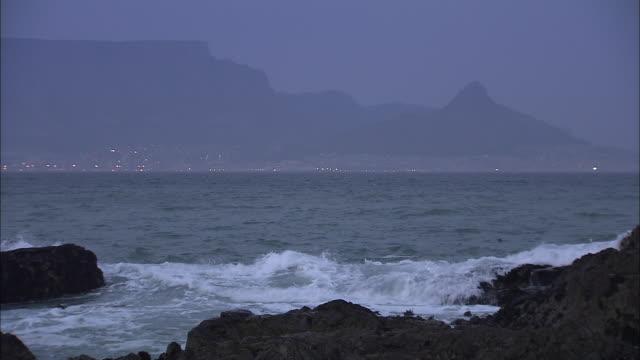 waves crash on a rocky shore. - 南ア テーブルマウンテン点の映像素材/bロール