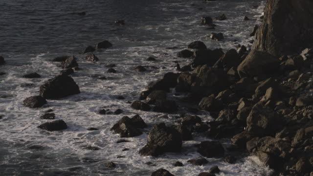 Waves crash on rocky shoreline