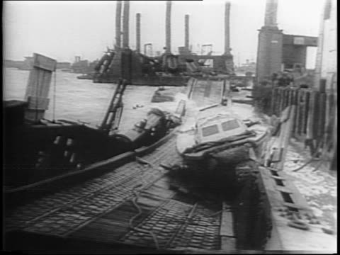 vídeos de stock e filmes b-roll de waves crash on sections of pre-fabricated harbor / storm wreckage in harbor includes boat washed onto dock / pan of harbor with ships and truck. - carroça puxada por cavalo