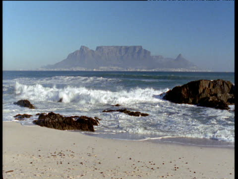 Waves crash on shore, Table Mountain in distance, South Africa