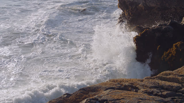 SLO MO. Waves crash on the rocks of an island shore.