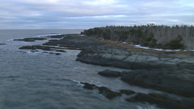 waves crash on the rocky shore of an island. - nova scotia stock videos and b-roll footage