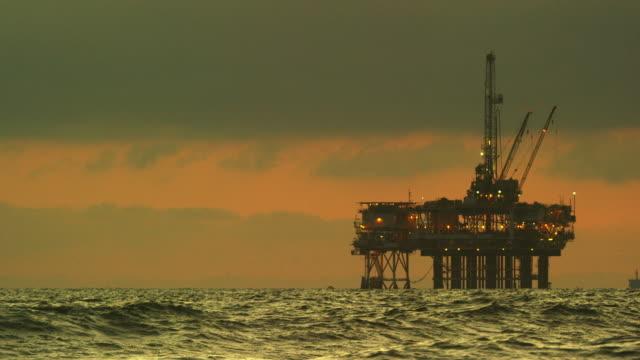 vídeos de stock, filmes e b-roll de ondas caem na costa de huntington beach no sul da califórnia com uma plataforma de perfuração de petróleo offshore no horizonte ao pôr do sol um céu dramático e tempestuoso - oleoduto
