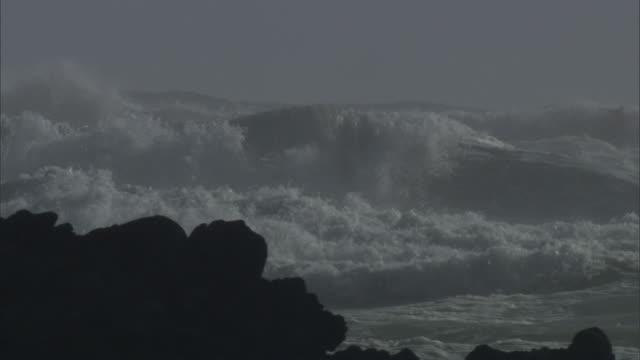Waves crash onto rocky coast during storm, New Zealand