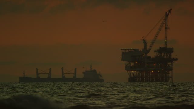 waves crash onto the shores of huntington beach in southern california with an offshore oil drilling rig platform and an oil (petroleum) tanker on the horizon in the distance  with seagulls flying at sunset under a dramatic, stormy sky - pump jack stock videos & royalty-free footage
