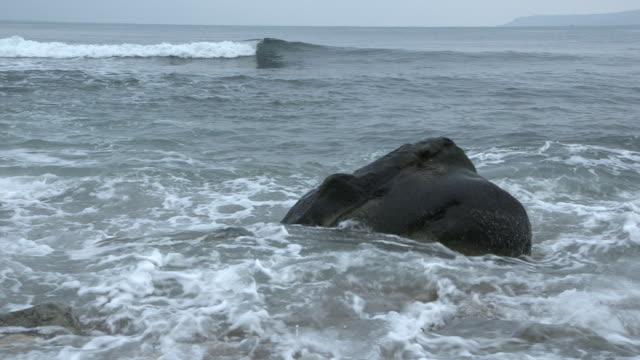 Waves crash over a large rock on a beach on the Dorset coast.