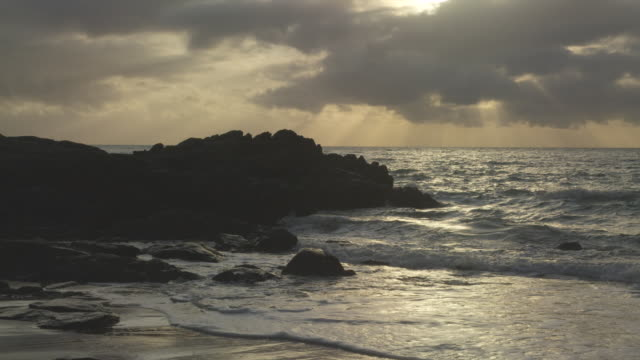 waves crash over rocks as sun sets - 1 minute or greater stock videos & royalty-free footage