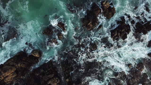 waves crash over the black rocks - aerial view - rough stock videos & royalty-free footage