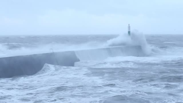 vídeos de stock, filmes e b-roll de waves crash over the stone jetty wall in aberystwyth wales as storm eleanor hits the uk causing power cuts and road disruption - aberystwyth