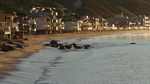 ms waves crashing against beach and homes at morning / malibu, california, united states - holiday villa stock videos & royalty-free footage