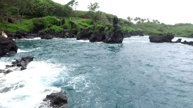 waves crashing against dark volcanic shoreline with lush landscape - butte rocky outcrop stock videos & royalty-free footage