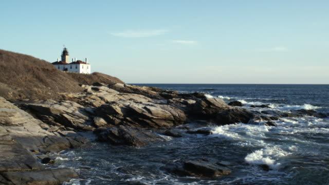 ws waves crashing against rocks, lighthouse in background, jamestown, newport, rhode island, usa - jamestown stock-videos und b-roll-filmmaterial