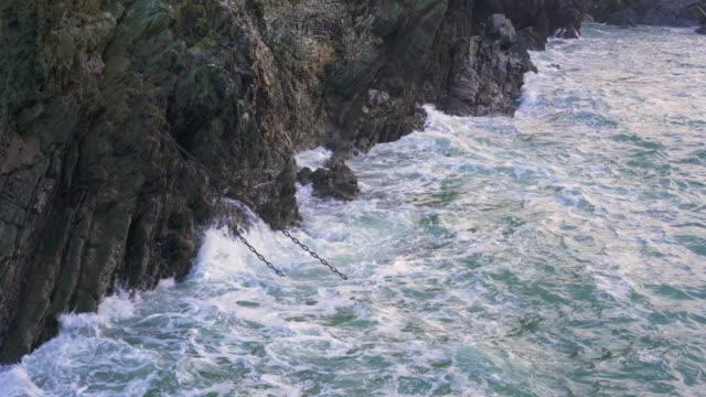 waves crashing against rocks - anchored stock-videos und b-roll-filmmaterial