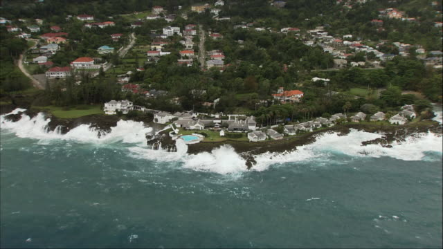 aerial, waves crashing against shore at holiday resort, jamaica - fan palm tree stock videos & royalty-free footage