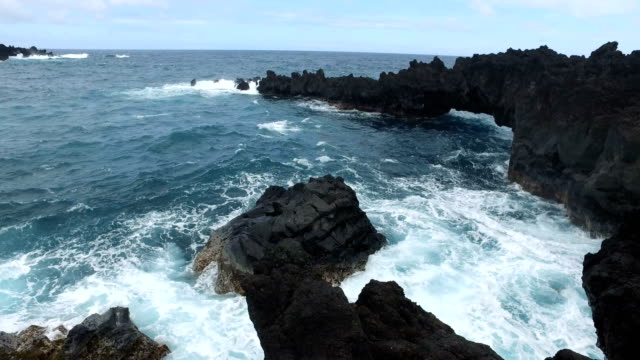 waves crashing against volcanic rock on maui island - butte rocky outcrop stock videos & royalty-free footage