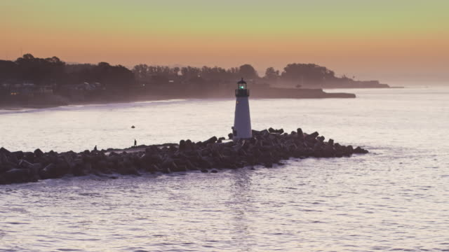 waves crashing around walton lighthouse, santa cruz at sunrise - drone shot - santa cruz california stock videos and b-roll footage