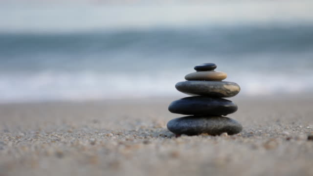 vidéos et rushes de ms waves crashing behind zen pile of stones/singapore - zen